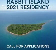 """A photograph of a green island surrounded by ocean reading """"Rabbit Island 2021 Residency Call For Applications""""."""