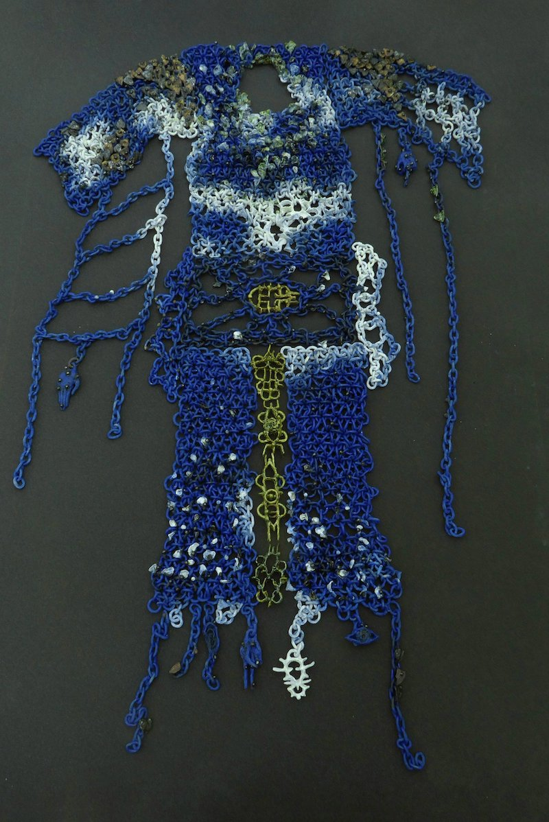 a close up detail of a wearable art work made of blue ceramic pieces