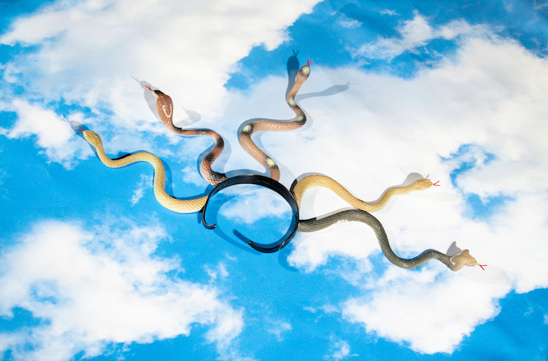 a headband with plastic snakes coming out of it, lies on top of a photograph of a blue cloudy sky