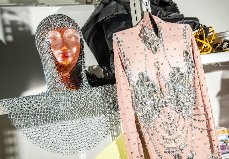 a chainmail hood and a sequined dress hang on a metal shelf