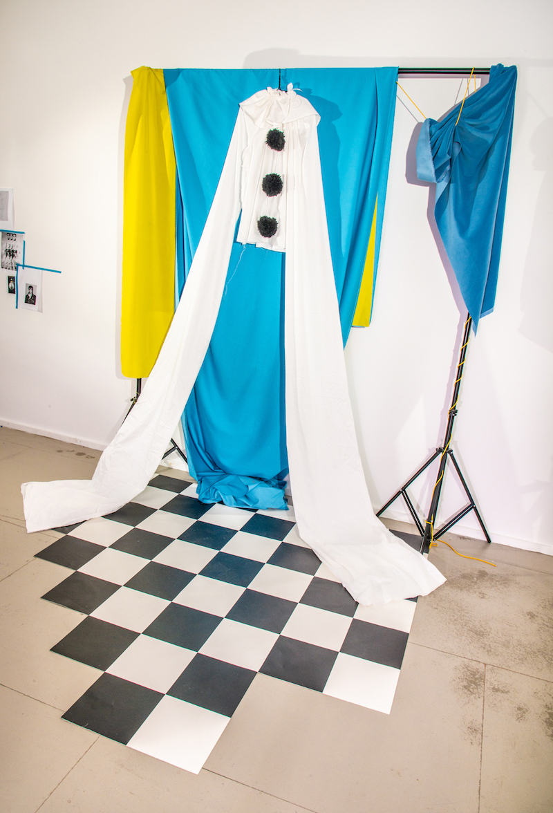 a long-armed white clown costume with black pompoms hangs in front of blue and yellow draped textiles, above a checkered floor