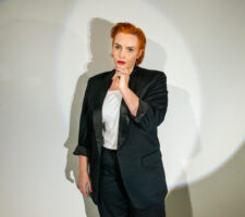 a person with short, sleek orange-colored hair stands in front of a circular stage light, wearing a black lounge suit and white shirt, she looks into the camera