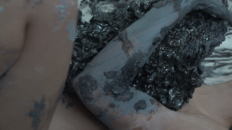 a close up still from a video, featuring some unidentifiable limbs covered in dark clay