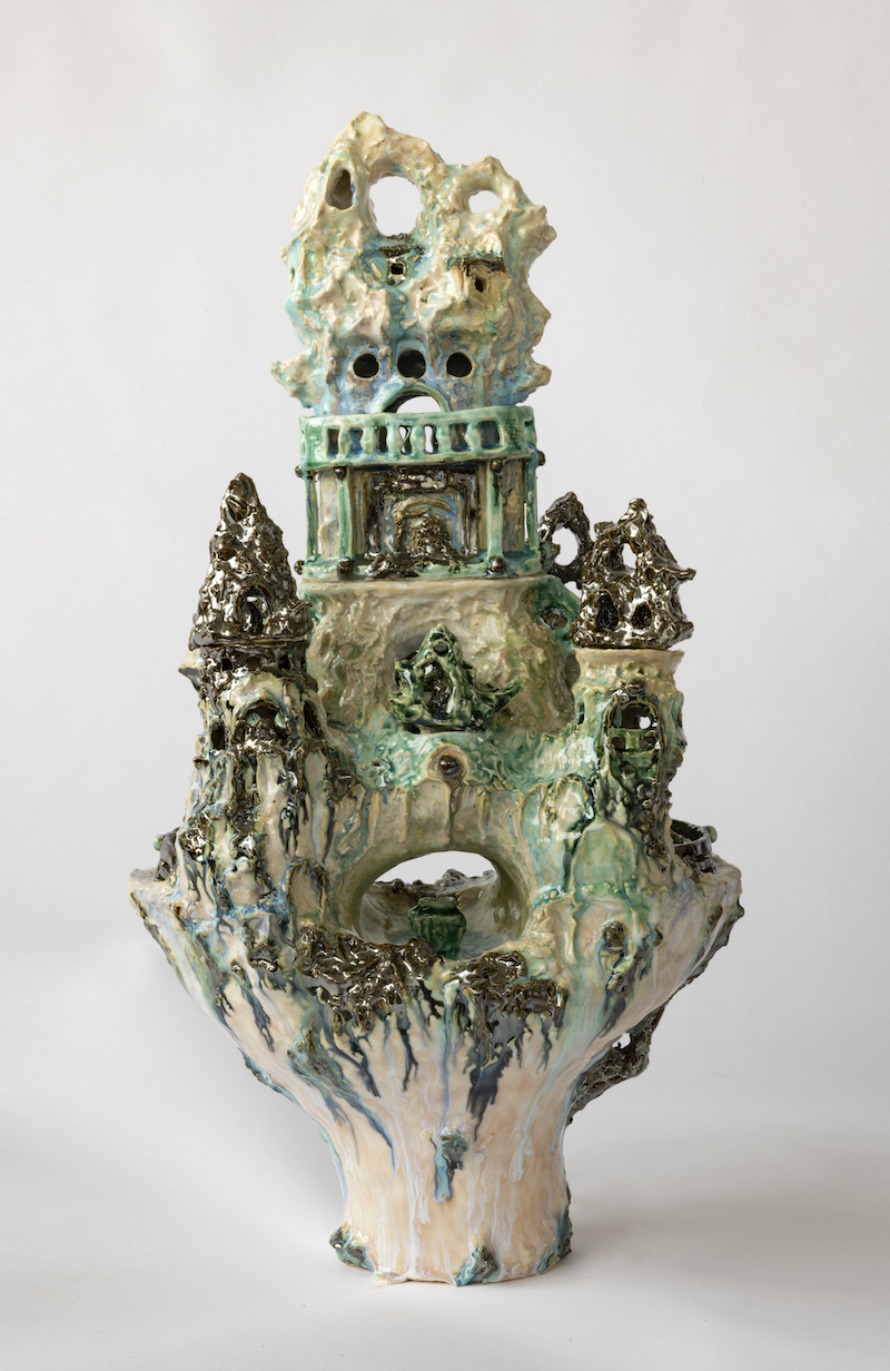 a detailed image of a ceramic vessel that looks like a small palace, in shades of beige and turquoise