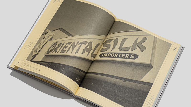 a photo of an open book, showing a photo of the Oriental Silk Importers shop sign spread across two pages, in a light yellow shade