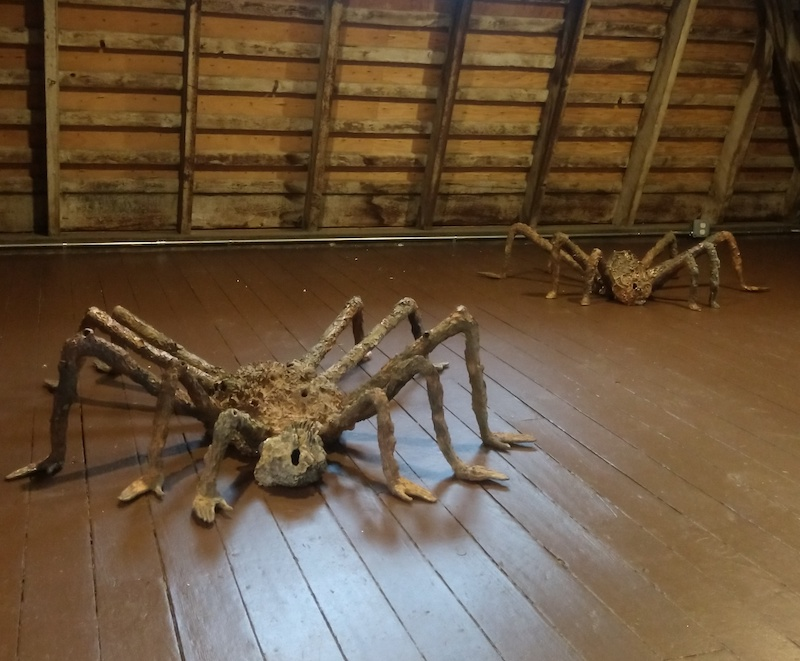 two large scale ceramic spiders positioned on a wooden attic floor