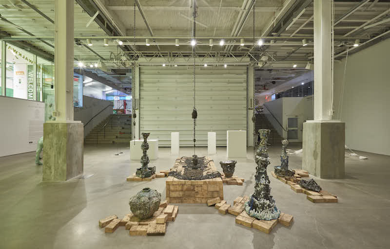 a view of several ceramic sculptures displayed in an exhibition room with two large columns framing them