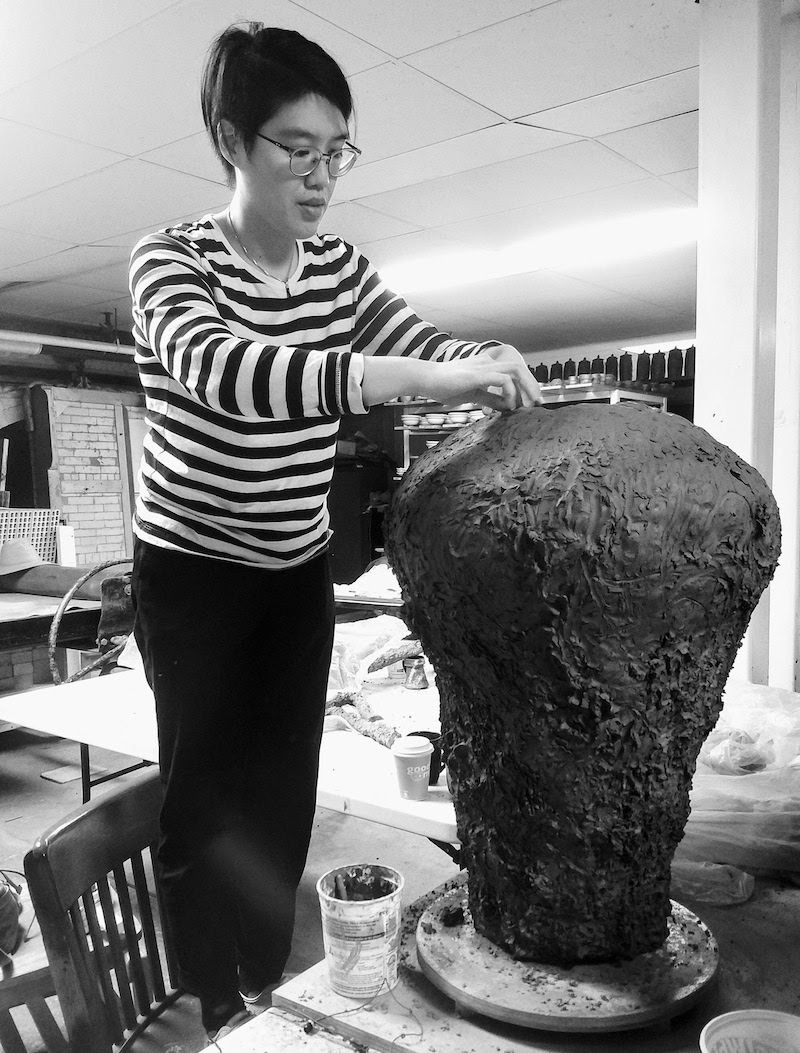 a black and white photo of the artist Heidi Lau shaping clay in her studio