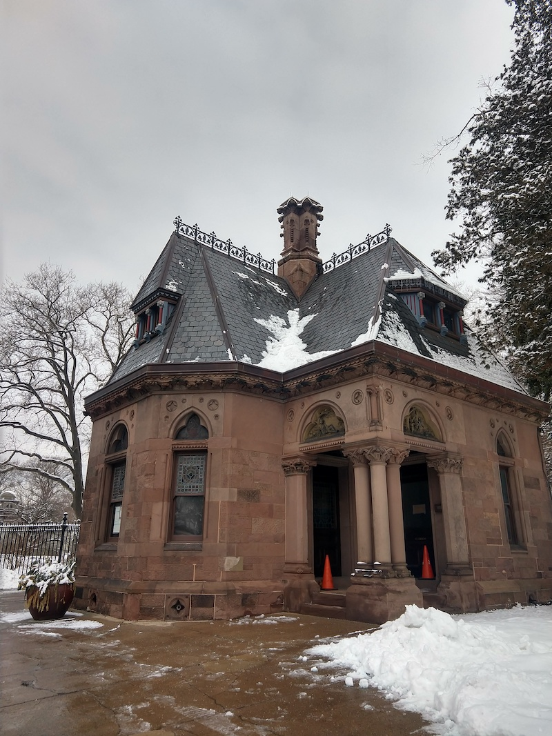 a photo of the cemetery studio space from outside, the building covered in snow