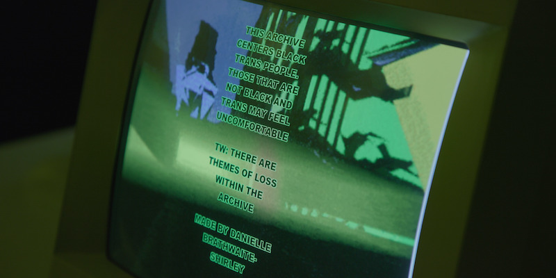 A computer screen with a green and black background with text from the artwork printed on it.