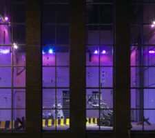 A view through the windows of KINDL at night with a purple light shining through the windows.