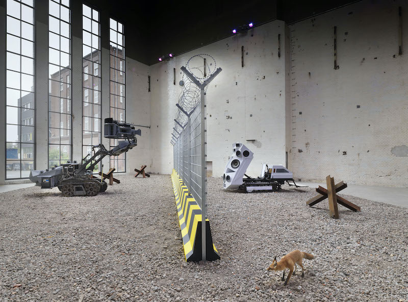 A view of the exhibition from inside with both works on either side of a barbed-wire fence.