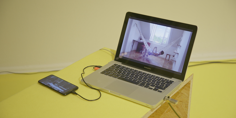 laptop and phone are sitting on a yellow bench depicting the artist in a hammock.