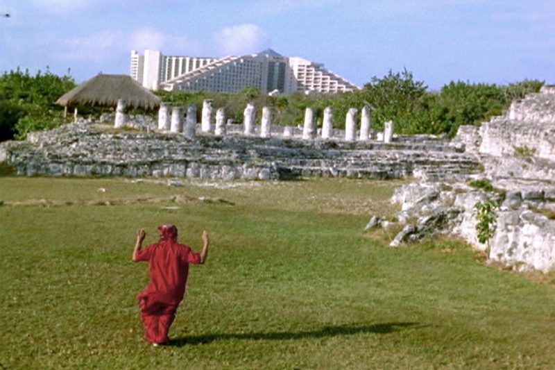 a person in red robes runs across a field towards white columns of mayan ruins in the background