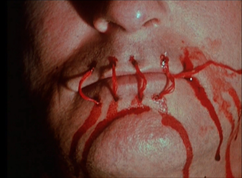 a close up of a person's mouth, with the lips sewn shut with bright red thread and a blood-like substance running down the cheeks and chin