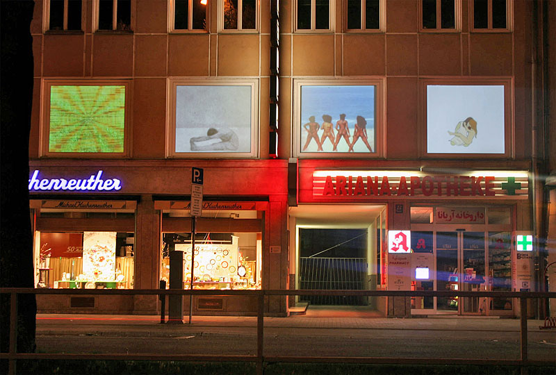 storefronts on a shopping street show video projections in their windows at night