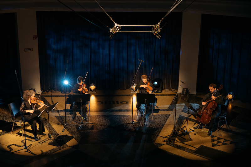 a quartet of musicians sit on chairs under stage lights in an otherwise dark room