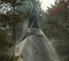 a video still of a Sami lavuu (tent) in a forest with mist rising up beside it