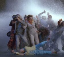 a video still of a group of people in a storm, a tableau that looks as if the people are being pushed and toppled by the wind