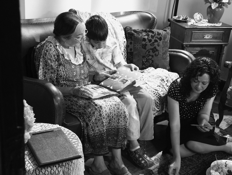 a black and white still of an older woman and a young kid sitting on a sofa looks at a photo album