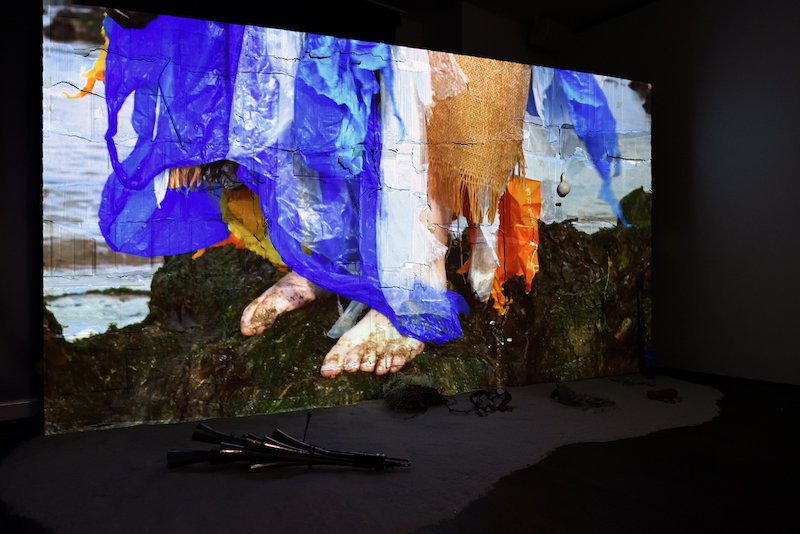 a photo of a video installation, projected on a wall, showing a persons feet shrouded in colorful blue and orange tattered fabrics