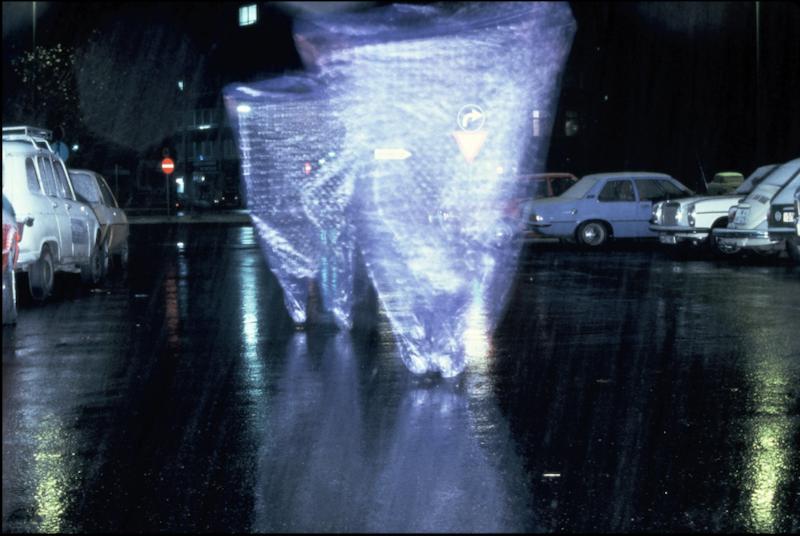 A tornado of plastic on a dark street in the rain.