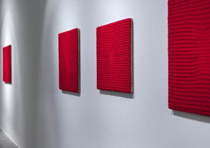 An installation view of 'Series #1-4' which is hanging red textile.