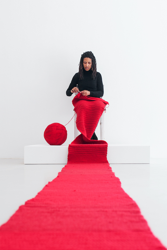 Lerato Shadi sits on a stage knitting a very long red textile.
