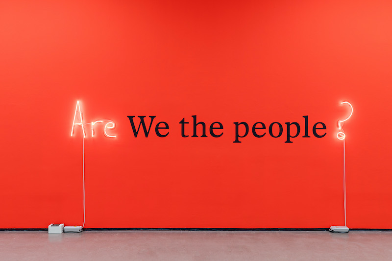 """Are we the people?"" is written on a red wall."