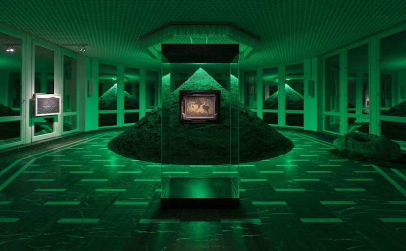 a large sand pyramid in the center of a room is illuminated with a green light, in front of it a small painting my Henri Rousseau is mounted on a clear glass wall