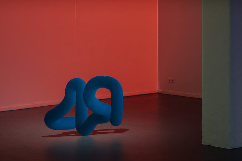 a squiggly blue sculpture sits on the floor in front of a red-list wall