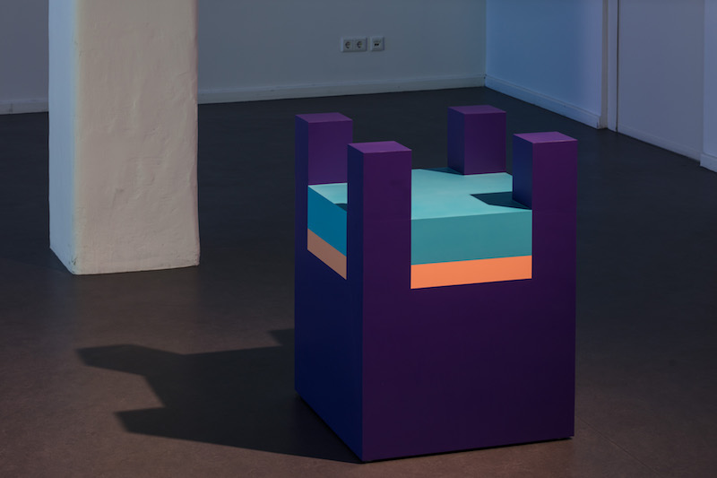 a boxy purple, pink and blue sculpture resembling a lego block sits on a concrete gallery floor