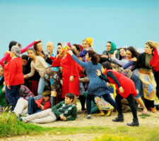 a group of people, some dressed in bright red, pose for a staged photo that looks as if in motion on a patch of grass