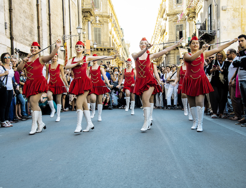 a group of majorettes march down a street wearing red uniforms and high white boots