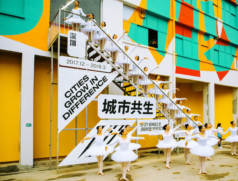 several ballerinas in white tutus hold their poses in front of a white staircase, a banner with chinese text hanging behind them