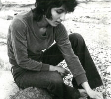 a black and white photograph of the poet Semra Ertan sitting on a log at the beach, looking down at a rock in her hand