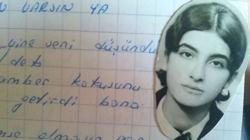 a photograph of the poet semra ertan pictured on top of a notebook of hand-written poetry
