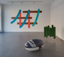 an installation view of the gallery's ground floor room with two colorful sculptures on the floor and a mounted abstract sign system