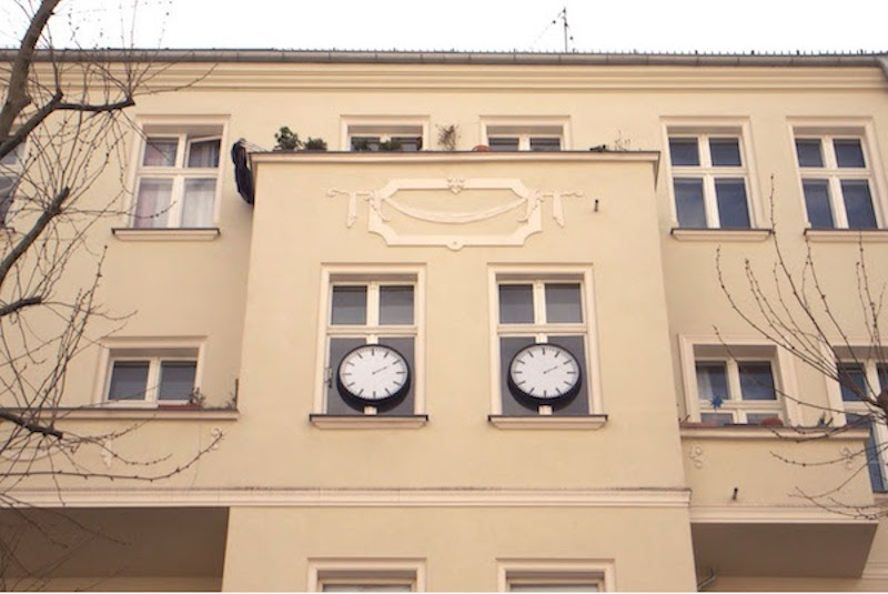 a building facade with two large black and white clocks installed on its windows