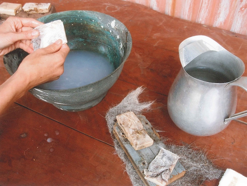 two hands over a wash basin, scrubbing with ass milk soap