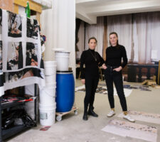 two artists stand in their studio space, next to shelves full of materials, both dressed in black
