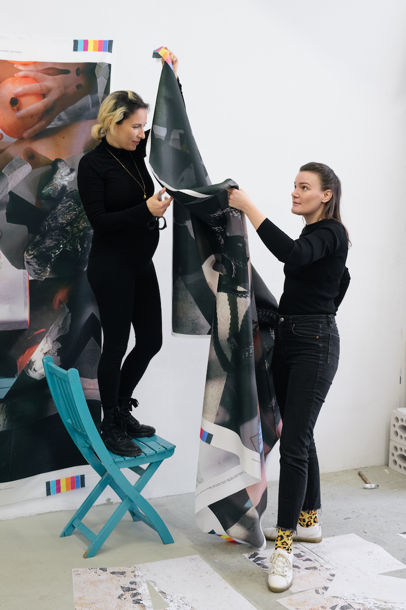 two artists hang a textile print on the wall, one standing atop a blue folding chair