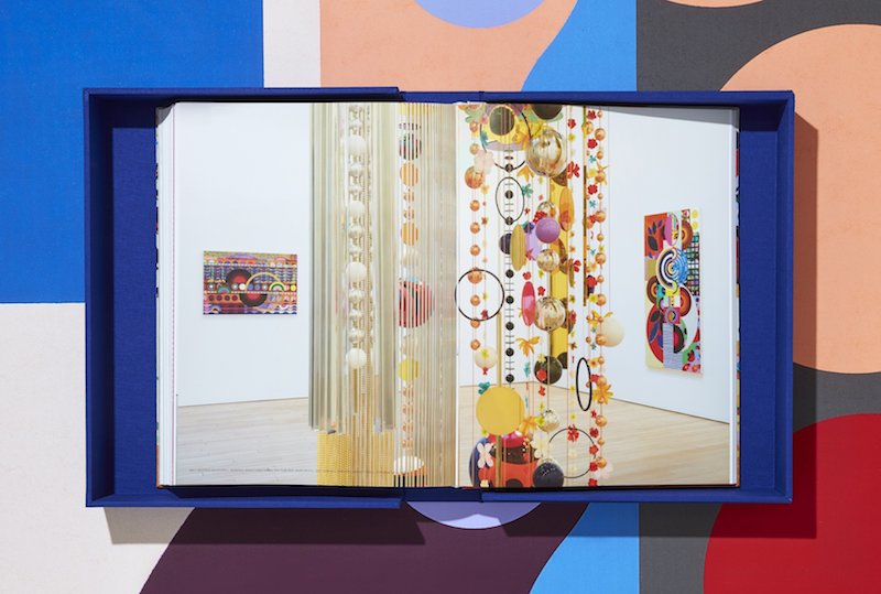 an inside spread of Beatriz Milhazes monograph showing an exhibition installation of her hanging sculptures and paintings