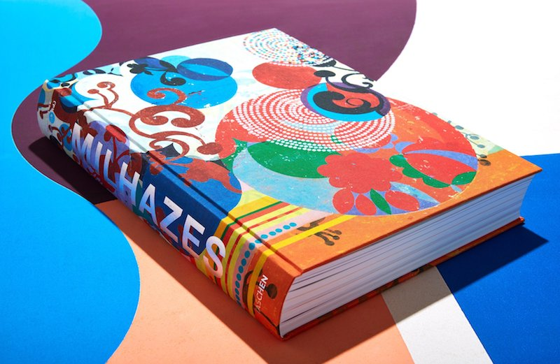 a colorful book of Beatriz Milhazes work photographed on a blue, purple, white and pink background