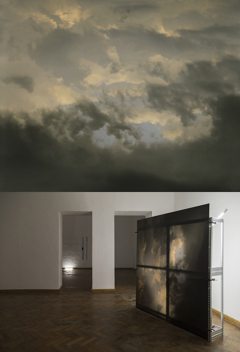 a photograph of a dark cloudy sky mounted on plexiglass in a gallery room