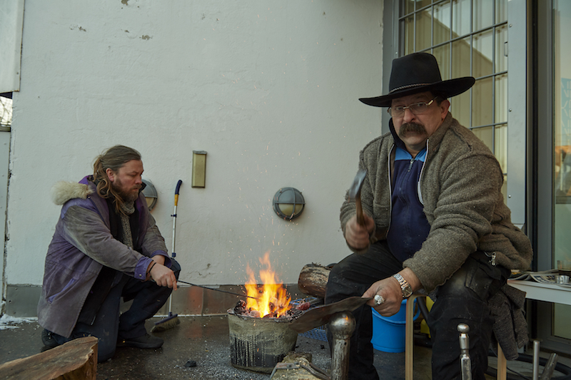 two people, one with a black cowboy hate, sit around a small fire in front of a government building