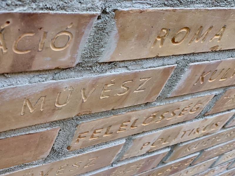 a close up image of a brick wall with Hungarian words written on it