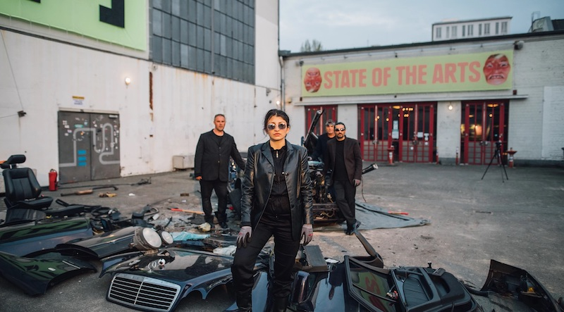 """a woman in full black leather and sunglasses stands authoritatively in front of a lot full of car parts and scrap metal, with several family members behind her and a sign in the background reading """"state of the arts"""""""