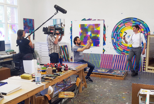 a film crew interviews an artist as they stand in front of their brightly colored artworks in their studio