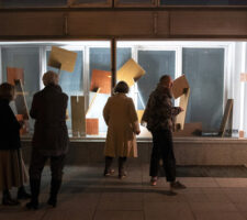 a group of four people stand on the street in front of a brightly-lit gallery window